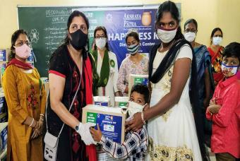 Children accompanied by their parents receive the Happiness Kits