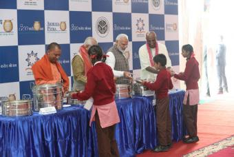 From left to right, Shri Yogi Adityanath, Shri Ram Naik, Shri Narendra Modi and Shri Madhu Pandit Dasa, serve hot nutritious Akshaya Patra food to the children