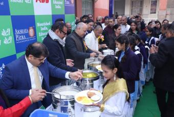 Beneficiary children being served by dignitaries