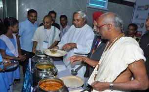 At the end of the inauguration, CM Patnaik and Madhu Pandit Dasa serve a meal to some of the government school students present at the inauguration