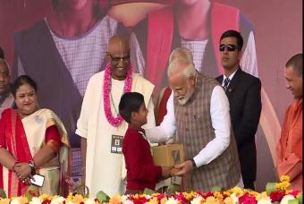 A child presents the Prime Minister with a '3 Billion Meals' memento