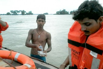 Food and water being transported in boats to flood affected villages