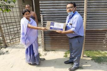 Akshaya Patra employees hand over grocery kits to a woman in need.