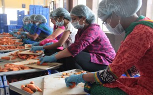 Volunteers are seen helping Akshaya Patra kitchen staff in prepping for the next day's meals
