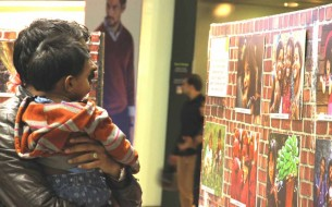 A father showing his child the pictures at the exhibition.