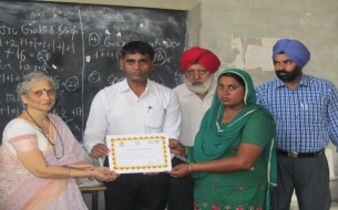 Haryana cook cum helper being appreciated with a certificate for being part of the Phase III training programme