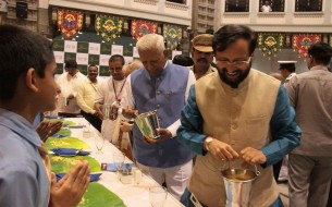 Shri Prakash Javadekar, Honourable Union Minister of Human Resource Development (right) and Shri Vajubhai Rudabhai Vala, Honourable Governor of Karnataka (second from right) serve Akshaya Patra beneficiary children